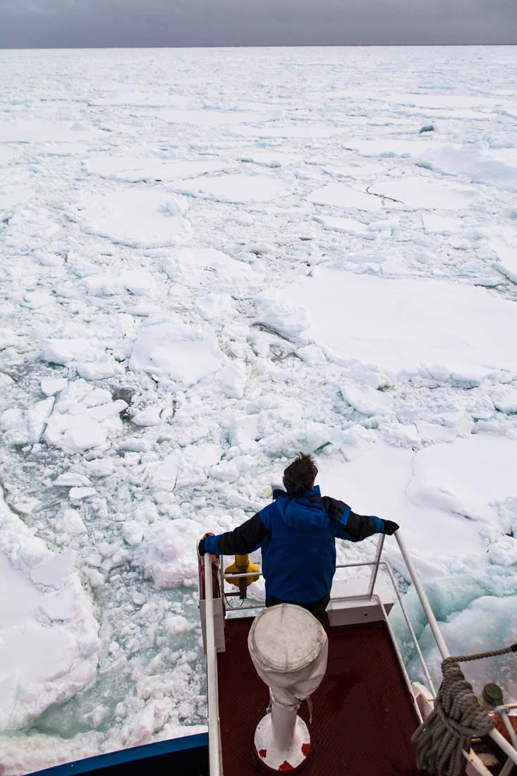 Un passager assiste de l'aileron aux manoeuvres de L' Astrolabe pour se frayer un chemin dans le pack (la glace de mer). 66 eme parallele sud, 11/02/2013 - ANTARCTIQUE.