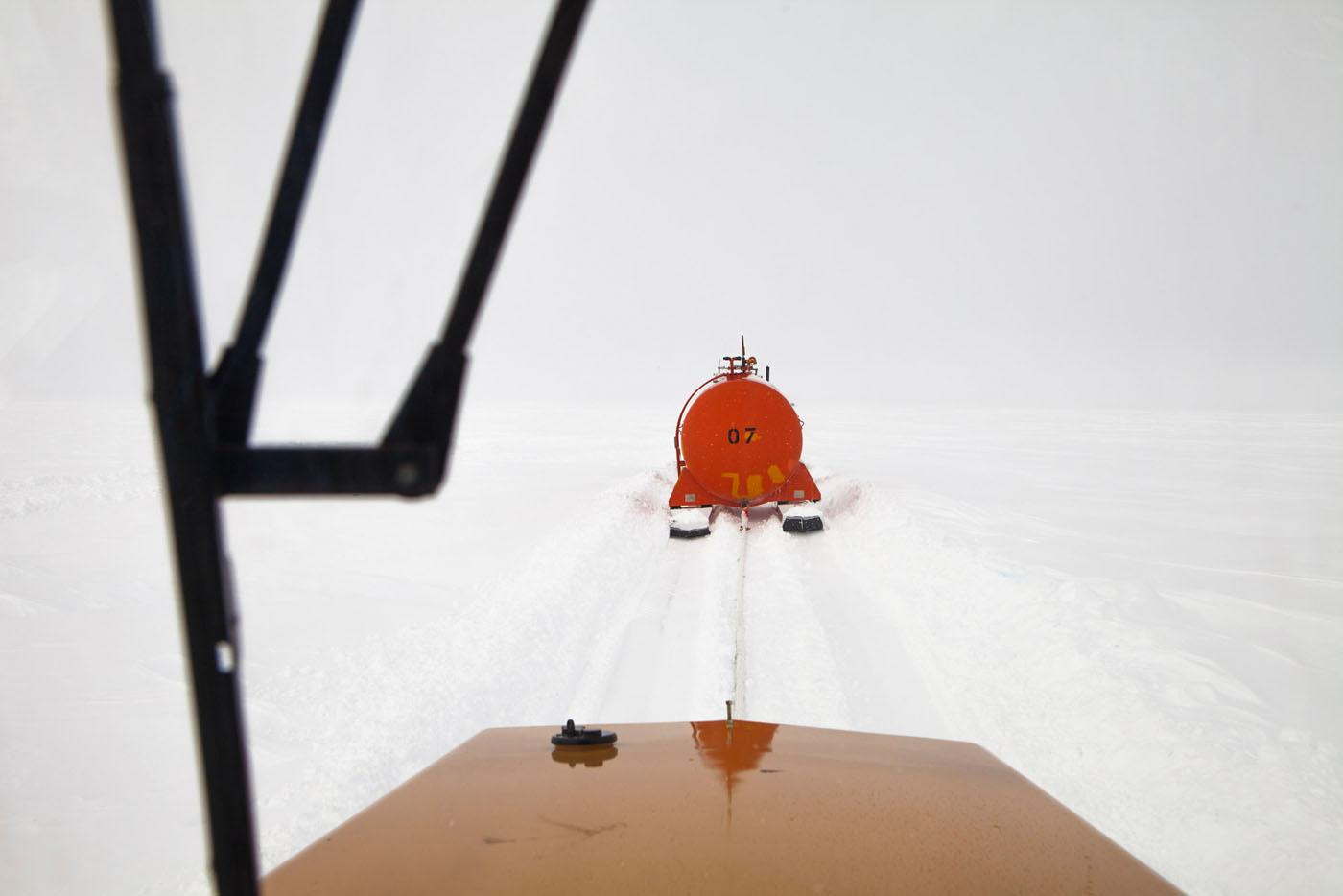 Une cuve de gasoil tractee par un tracteur vue de la cabine d'un tracteur de tete sur le raid de ravitaillement de la station Franco-Italienne Concordia. Antarctique, 02/02/2013